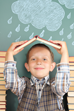 bad weather: Cheerful school concept with the boy joker who hides from bad weather under a roof from the textbook Stock Photo