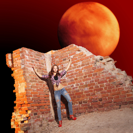 futuristic girl: Sexy girl in torn jeans amid ruins on futuristic Martian background Stock Photo
