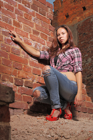 impassioned: Sexy girl in ragged jeans on old ruins