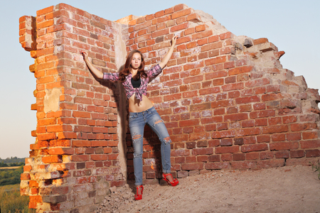 impassioned: Sexy girl in torn jeans on old ruins Stock Photo