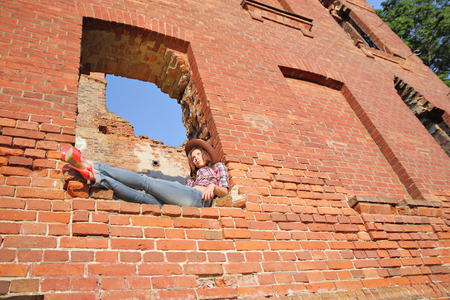 impassioned: Attractive girl in torn jeans in window of old ruins Stock Photo