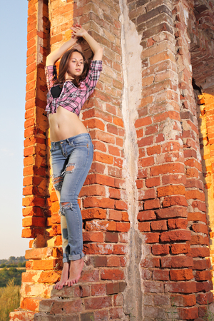 impassioned: Attractive girl in ragged jeans on old ruins