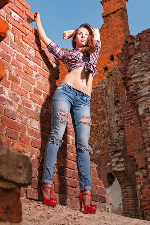 impassioned: Attractive girl in torn jeans in the ruins Stock Photo