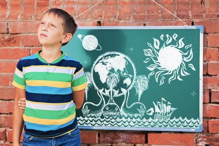 hereafter: Meditative boy near chalkboard with drawing Earth map on three whales in the improvised outdoor class