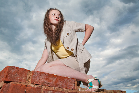 dreaminess: Fashionable girl posing on old brick wall on sky background