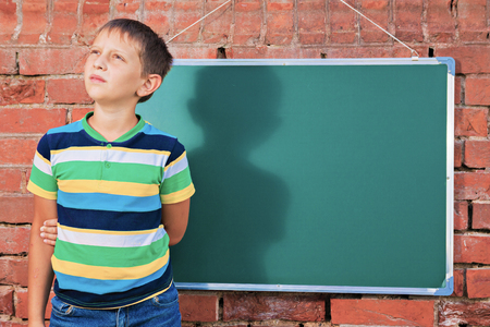 prospection: Meditative boy near chalkboard with copy-space in the improvised outdoor class Stock Photo