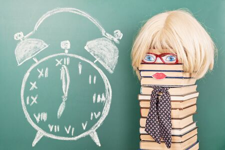 Funny education idea, unusual woman teacher in front of blackboard with alarm clock drawing Stock Photo