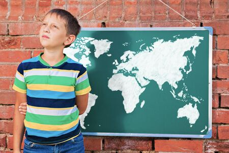 hereafter: Meditative boy near chalkboard with drawing Earth map in the improvised outdoor class