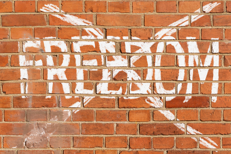 Brick wall with the crossed out word FREEDOM