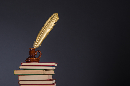 Education and information concept, literature and poetry idea. Books and inkwell with a golden quill pen on top