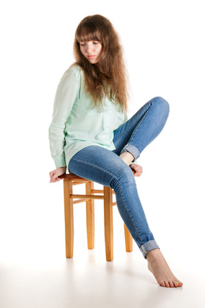 Attractive barefoot girl sitting on stool
