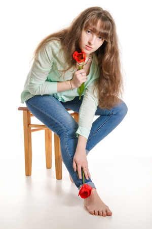 Attractive girl sitting on stool with tulips in hand