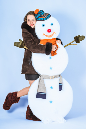 Pretty girl with her friend snowman Stock Photo