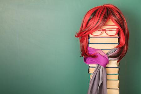 Unusual Beautiful Teacher Girl with Luxurious Red Hair. Copy space on blackboard