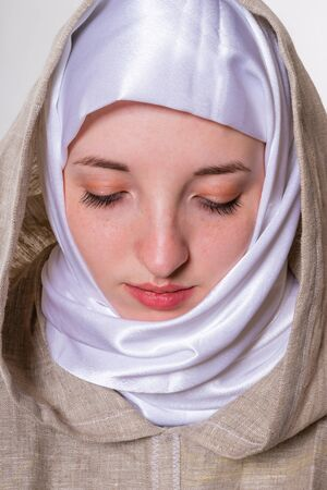 Lovely pure girl in monastic clothes and white scarf
