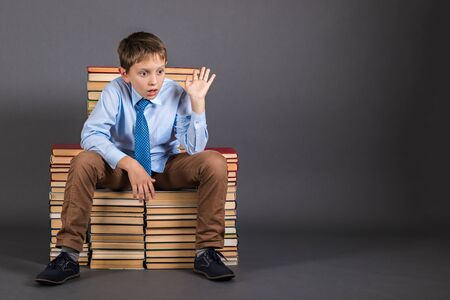 Education idea. The boy sitting on the throne from the books, who was suddenly visited by a brilliant idea