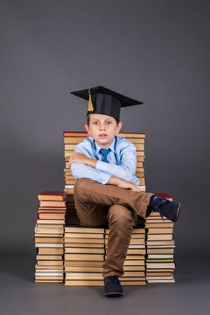Education concept. Boy sitting on a throne from books with his legs cross