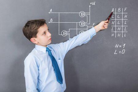 A boy studying digital chips on CMOS transistors