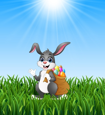Easter bunny rabbit with easter eggs a sack of full in the grass background Stock Photo