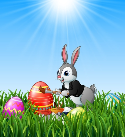 Easter bunny painting easter eggs in the grass background