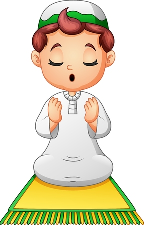 Muslim kid sitting on the prayer rug while praying Stock Photo