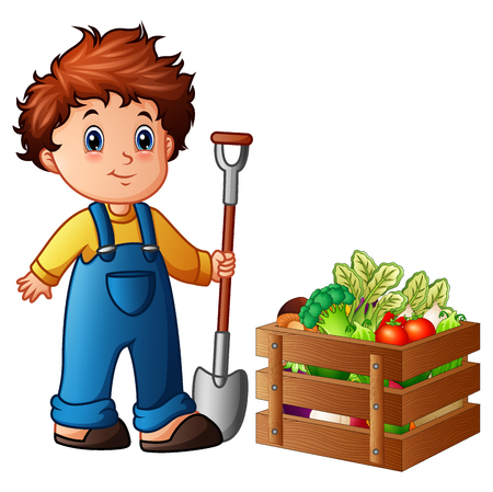 Boy farmer holding shovel with vegetables in a wooden crate Stock Photo