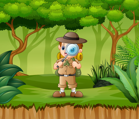 Boy explorer with magnifying glass in the forest