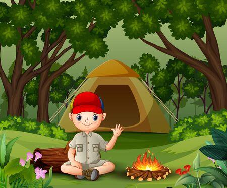 Scout de garçon s'asseyant près du feu de camp