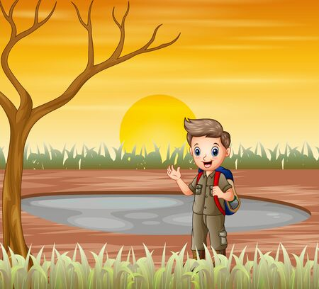 The scout boy standing under a dry tree