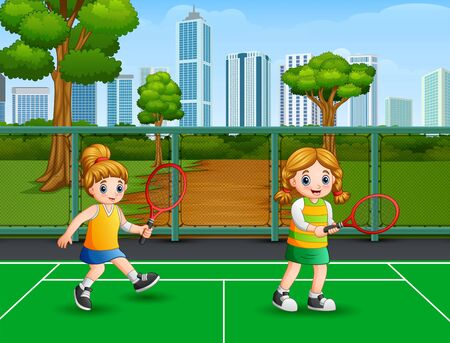 Happy girls playing tennis at the court