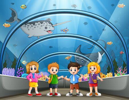 Funny school children looking at fish in aquarium
