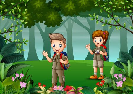 Scout boy and girl in uniform exploring the forest