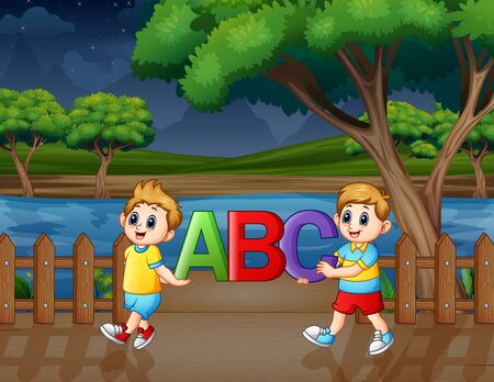 Happy children holding ABC text in the park