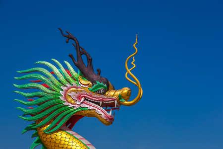 Golden dragon statue on bule sky in the winter