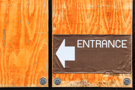 The signboard of entrance on the wall with plywood.