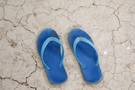 Two old sandals to lay down on arid ground.