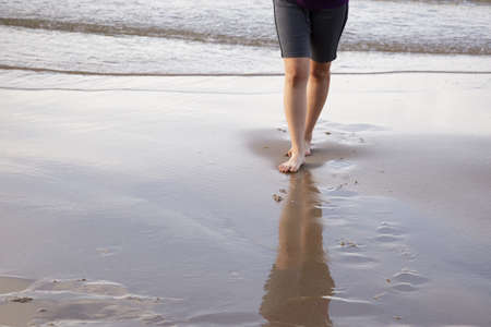 Woman walking on the beach and beautiful footprint in the sand at sea.