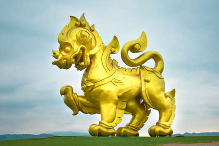 Big golden lion in width green field and sky sunset view in the background, Chiang Rai, Thailand. Stock Photo