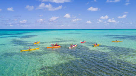 Aerial view of tropical island at Glovers Reef Atoll in Belize with a group of kayakers