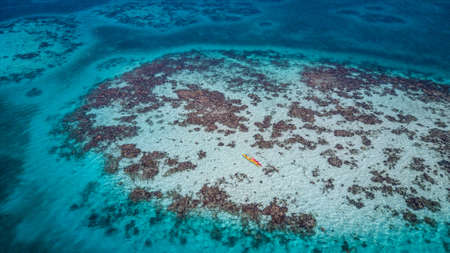 Aerial view of tropical island at Glovers Reef Atoll in Belize with two kayaks over a patch reef