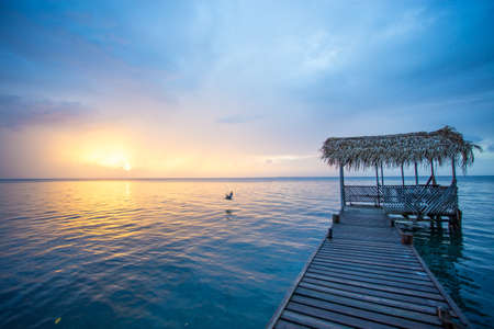 A bird is flying in the scene showing a wooden dock with a palapa roof and sunset. The water is calm and blue.