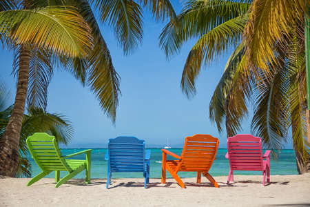A tropical beach island with beautiful sand and turquoise water with palm trees. It the South Water Caye island in Belize and its a typical Caribbean island. Imagens