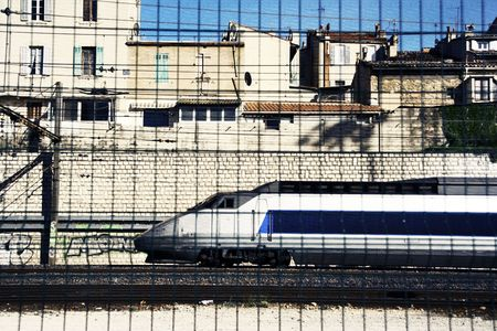 the  then: a train in marseille, shot through a mesh fence in the forground, then filtered