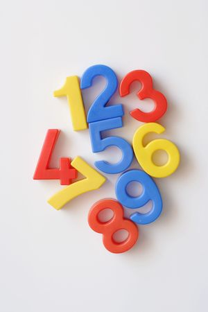 disarray: number fridge magnets displaying 1- 9 in a messy arrangement