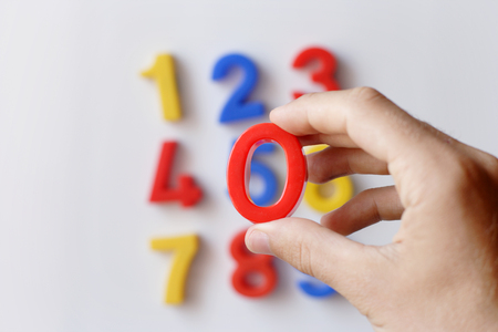 sums: number fridge magnets displaying 1 - 9, hand in focus holding 0