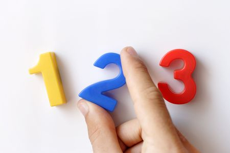 sums: number fridge magnets displaying 1 2 3, hand holding the number 2 Stock Photo