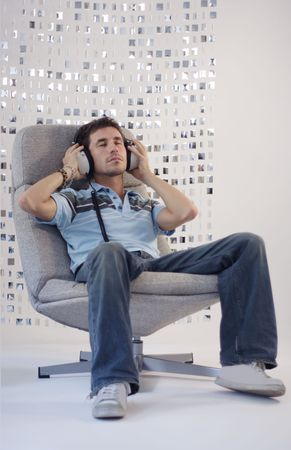 relaxes: a man relaxes in a chair listening to music Stock Photo
