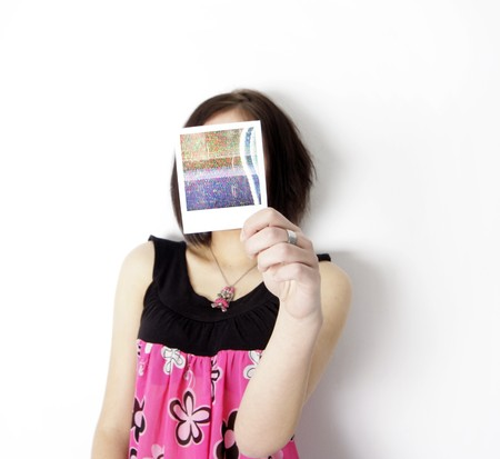 fuzz: a young woman holds a poloroid in front of her face Stock Photo