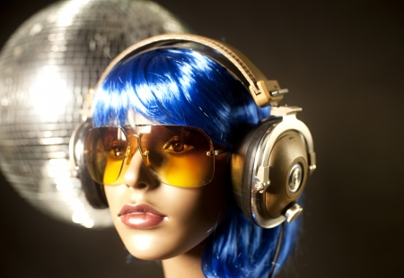 hedonistic: a cool female mannequin head with headphones and discoball in background Stock Photo