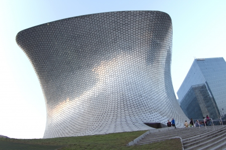 the very modern building soumaya museum in mexico city, during sunset. scene turns from day to night